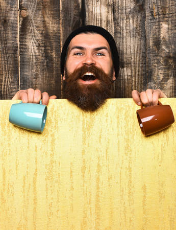 haircut: Bearded man, long beard. Brutal caucasian smiling happy unshaven hipster in black hat with yellow paper sheet holding colorful cups on brown vintage wooden background, copy space