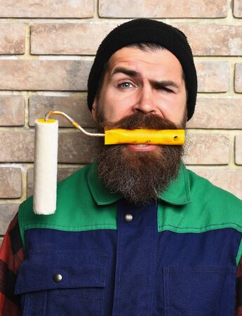 haircut: bearded painter man, long beard, brutal caucasian hipster with moustache in black cap holding in his mouth roller paint with satisfied face on brick wall studio background Stock Photo