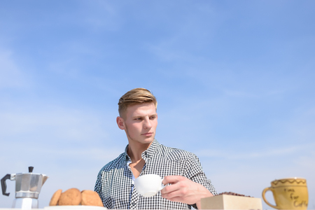 stylish caucasian man in checkered shirt having breakfast on roof with cup of coffee or tea and cookies, coffee maker, book with serious face on blue sky background