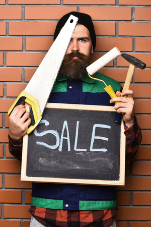 haircut: bearded builder man, long beard, brutal caucasian hipster with moustache holding various building tools: saw, hammer, roller paint, board with inscription sale, surprised face on brick wall background Stock Photo