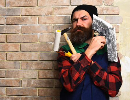 haircut: bearded painter man, long beard, brutal caucasian hipster with moustache in uniform holding various building tools: hammer, roller paint and spatulas with serious face on brick wall studio background