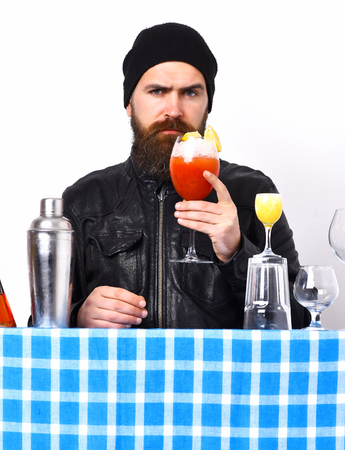 Bearded man, long beard. Brutal caucasian hipster with moustache in rock black style holding beverage or fresh cocktail and bar stuff with alcohol shot on blue checkered plaid isolated on white