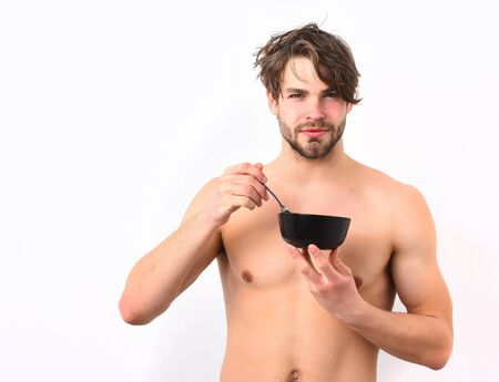 Bearded man, short beard. Caucasian sexy young macho with stylish hair, moustache on serious face shows muscular torso holding black bowl with fork isolated on white studio background