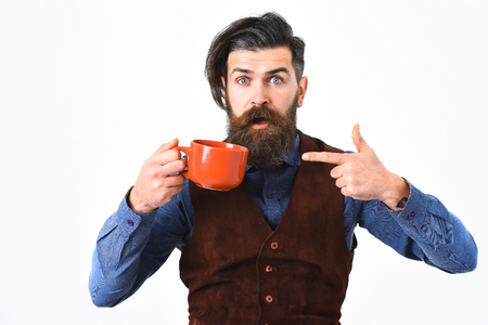 haircut: bearded man, long beard, brutal caucasian hipster with moustache holding mug or cup with coffee, tea with surprised face isolated on white background Stock Photo