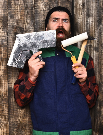 hair roller: bearded builder man, long beard, brutal caucasian hipster with moustache in uniform holding various building tools: hammer, roller paint, spatulas with surprised face on brown wooden studio background