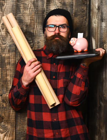 Bearded man, long beard. Brutal caucasian serious unshaven hipster holding craft paper rolls, piggy bank on laptop in checkered shirt with hat and glasses on brown vintage wooden studio background