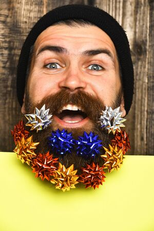 Bearded man, long beard. Brutal caucasian happy smiling hipster with colorful gift decoration stars in moustache, yellow paper sheet on brown wooden vintage studio background 版權商用圖片
