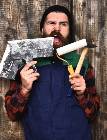 bearded builder man, long beard, brutal caucasian hipster with moustache in uniform holding various building tools: hammer, roller paint, spatulas with satisfied face on brown wooden studio background 版權商用圖片