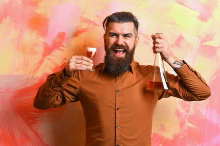 Bearded man, long beard. Brutal caucasian smiling happy hipster with moustache in brown shirt holding alcoholic red shot and glass tube or flask on colorful texture background 版權商用圖片