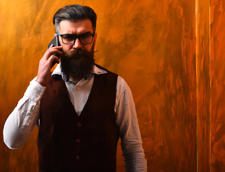 Bearded man, long beard. Brutal caucasian unshaven serious hipster with glasses and moustache talking by cell phone, wearing white shirt, suede waistcoat on brown studio background