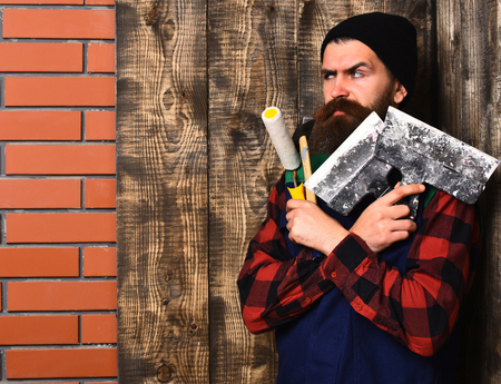 bearded foreman, long beard, brutal caucasian hipster with moustache in uniform holding various building tools: hammer, roller paint, spatulas with serious face on brick wall wooden studio background