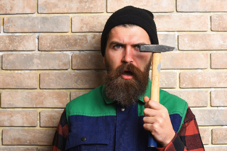 bearded worker man, long beard, brutal caucasian hipster with moustache in black cap holding hammer with serious face on brick wall studio background