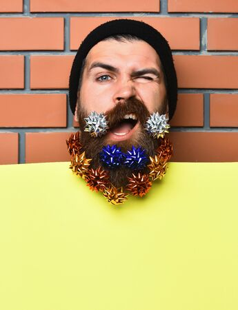 Bearded man, long beard. Brutal caucasian squinting hipster with colorful gift decoration stars in moustache, yellow paper sheet on brown brick wall studio background