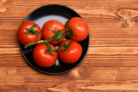set of red fresh tomatoes on vine on plate on brown vintage wooden background. cooking concept Stock Photo