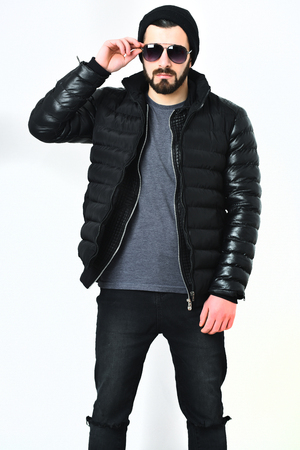 Bearded man, short beard. Brutal caucasian serious hipster with moustache wearing black nylon jacket, cap and sunglasses isolated on white background. Fashion show concept. Stock Photo