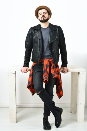 Bearded man, short beard. Caucasian serious hipster with moustache and brown hat wearing black leather jacket, checkered red shirt and ripped jeans isolated on white background
