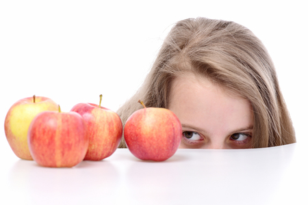 cute tricky girl hiding behind red apple fruit isolated on white background, harvest, copy space