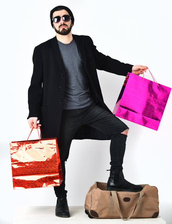 Bearded man, short beard. Caucasian hipster with moustache in sunglasses, leaning on stylish bag, holding red and pink shopping packages, isolated on white background