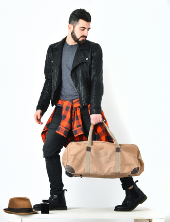 Bearded man, short beard. Caucasian hipster with moustache holding stylish bag, wearing black leather jacket, checkered red shirt and ripped jeans isolated on white background