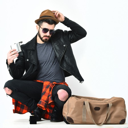 Bearded man, short beard. Caucasian hipster with moustache holding flask in sunglasses, black leather jacket, checkered red shirt and ripped jeans near stylish bag isolated on white, lookbook concept