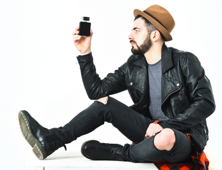 Bearded man, short beard. Caucasian serious hipster with moustache and brown hat holding perfume bottle, in black leather jacket, checkered red shirt, ripped jeans isolated on white background