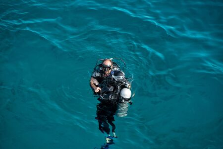 Hurghada, Egypt - February 24, 2017: underwater, snorkeling diver, man in wetsuit with snorkel, scuba, aqualung, mask swimming in sea or ocean on sunny day on blue background. Idyllic summer vacation