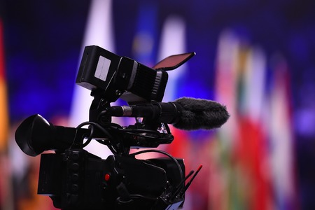 Modern digital television or video camera, camcorder, recorder in studio on blurred colorful background. Broadcasting, media, entertainment Stock Photo