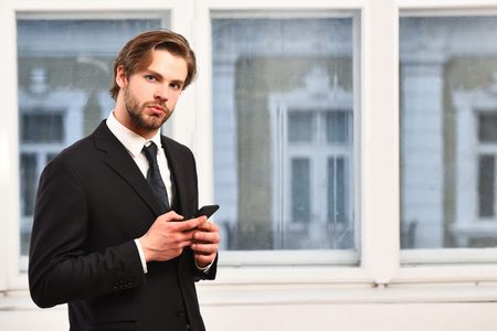 technology and people concept, serious businessman with smartphone talking in office near window, businessman, copy space Stock Photo