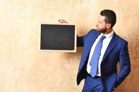 real leader: man in blue suit with blackboard, businessman with board in office, copy space Stock Photo
