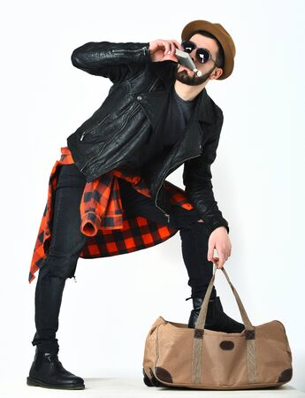 Bearded man, short beard. Caucasian hipster with moustache drinking from flask in sunglasses, black leather jacket, checkered red shirt, ripped jeans and brown hat isolated on white, lookbook concept