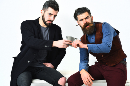 injurious: Two bearded mens, short and long beard. Caucasian stylish hipsters with moustache, holding flask with alcohol drink and cigar isolated on white background