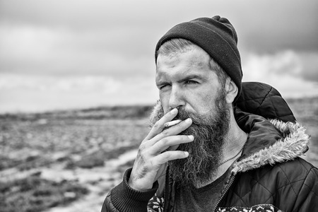 young bearded hipster man smoking cigarette in hat and jacket at mountain and cloudy sky on natural background, copy space