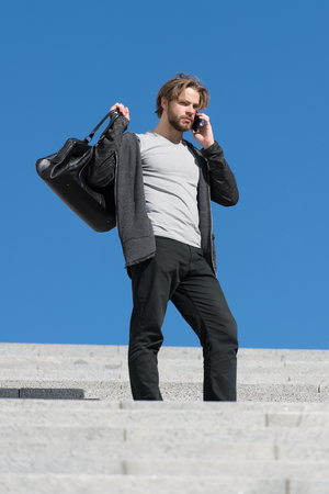 guy on stairs with phone, thoughtful young man sitting on a flight of steps staring into the distance with a serious expression against a blue sky background, guy with sport bag, copy space Stock Photo