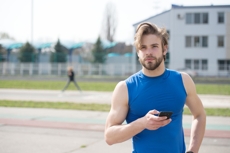 summer activity and sport. healthy lifestyle and communication, athletic bearded man or sexy handsome guy with muscular body holds mobile or cell phone training sunny outdoor in blue sportswear