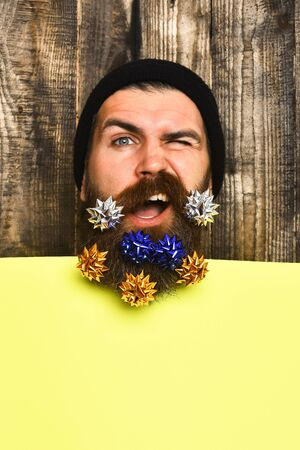Bearded man, long beard. Brutal caucasian squinting hipster with colorful gift decoration stars in moustache, yellow paper sheet on brown wooden vintage studio background