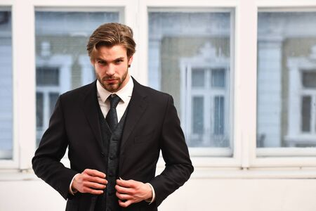 man or businessman with beard on serious face in black jacket, tie on window background, business concept