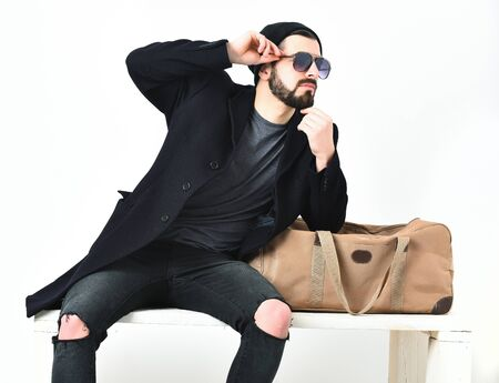 Bearded man, short beard. Caucasian hipster with moustache in sunglasses, leaning on stylish bag, wearing black jacket, cap and ripped jeans, isolated on white background Stock Photo