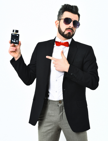Bearded man, short beard. Caucasian serious hipster with moustache and sunglasses standing and holding perfume bottle, wearing black jacket, white shirt and red bow tie isolated on white background