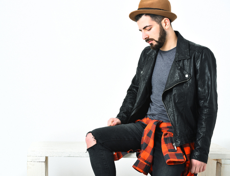 Bearded man, short beard. Caucasian serious hipster with moustache and brown hat, wearing black leather jacket, checkered red shirt and ripped jeans isolated on white background