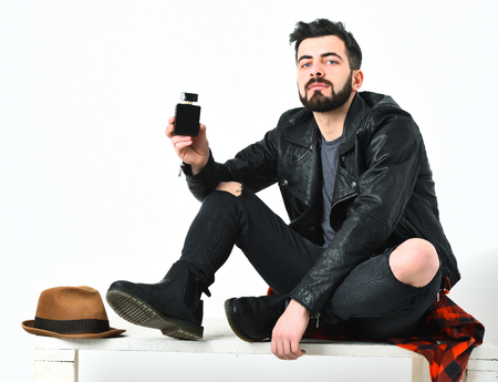 Bearded man, short beard. Caucasian serious hipster with moustache holding perfume bottle, wearing black leather jacket, checkered red shirt and ripped jeans isolated on white background Stock Photo