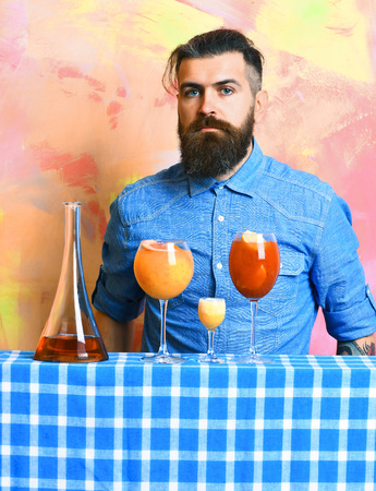 Bearded man, long beard. Brutal caucasian hipster with moustache in denim shirt and alcohol shot, fresh cocktails with bar stuff on blue checkered plaid on colorful texture background