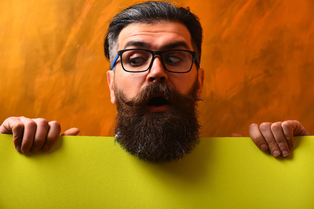 Bearded man, long beard. Brutal caucasian unshaven surprised hipster with glasses and moustache holding yellow paper sheet on brown studio background Stock Photo