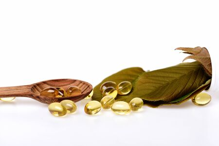 fish oil omega 3 gel capsules isolated on white background in wooden spoon with green leaves, copy space