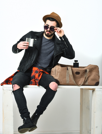 Bearded man, short beard. Caucasian hipster with moustache holding flask, in sunglasses, black leather jacket, checkered red shirt, ripped jeans and brown hat isolated on white, lookbook concept