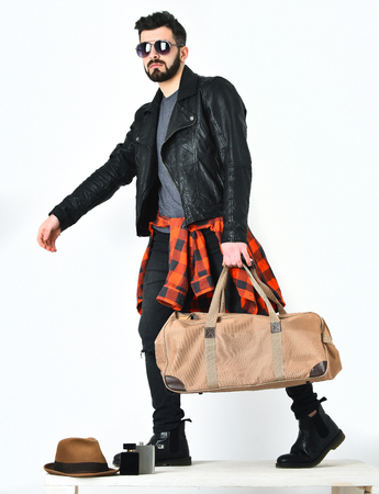 Bearded man, short beard. Caucasian hipster with moustache holding stylish bag, wearing black leather jacket, checkered red shirt, ripped jeans and sunglasses isolated on white background