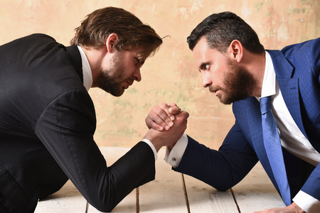 opposition of businessmen or men in suit, arm wrestling and power, business situation