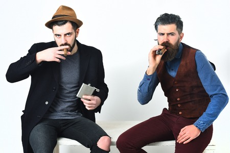 injurious: Two bearded mens, short and long beard. Caucasian stylish hipsters with moustache, holding flask with alcohol drink and smoking cigar isolated on white background