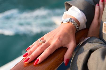 Mani femminili e orologio da polso con il manicure rosso e anello d'oro al dito con diamanti in prossimità di acqua Archivio Fotografico - 77907694