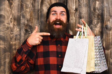 Bearded man, long beard. Brutal caucasian smiling happy hipster with moustache holding shopping packages in red black checkered shirt on brown wooden vintage studio background Stock Photo