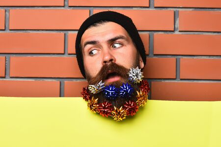 Bearded man, long beard. Brutal caucasian surprised hipster with colorful gift decoration stars in moustache, yellow paper sheet on brown brick wall studio background